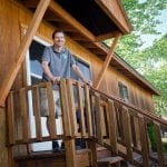 Man standing on front porch of home